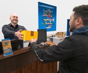 simon kühn übergibt ein gelbes paket an einen kunden